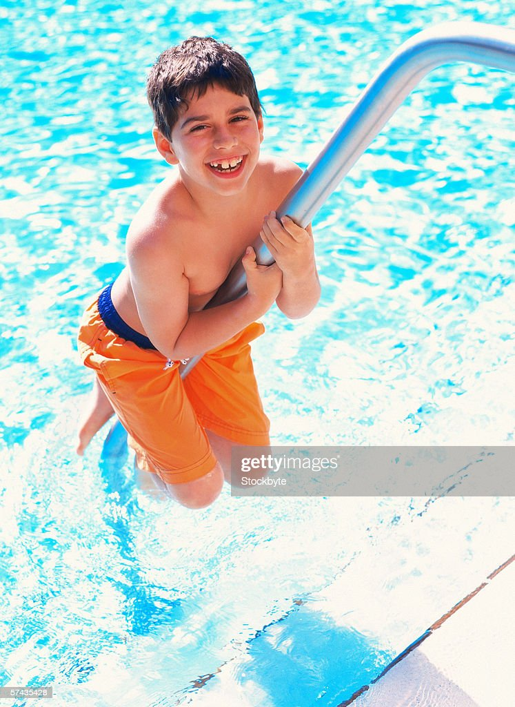 a young boy climbing on a swimming pool ladder : Stock Photo