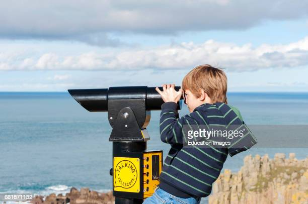 a young boy looking through a telescope at Lands End in Cornwall England UK