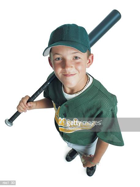 a young caucasian boy is wearing a green little league uniform and holding a bat over his shoulder as he smiles up at the camera