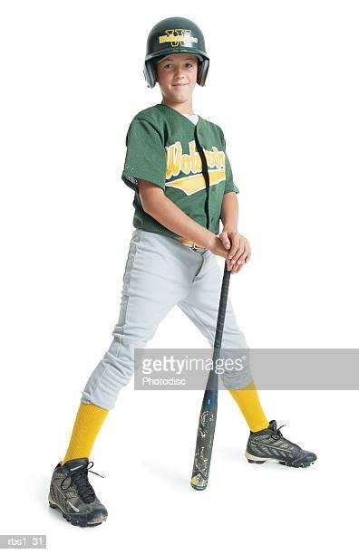 a young caucasian boy is wearing a green little league uniform and stands leaning on a bat while wearing a green batting helmet