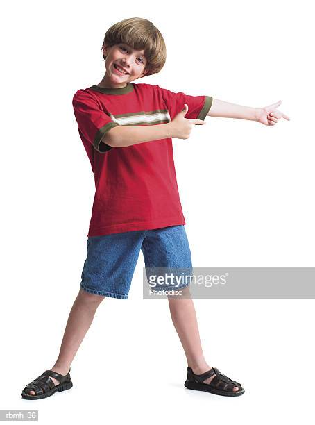 a young caucasian boy wearing jean shorts and a red shirt stands with his legs spread shoulder width apart and holds his arms out to one side indicating a product