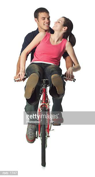 a young caucasian couple ride a bike together as they lovingly look into each others eyes