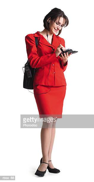 a young caucasian female business woman in a red dress writes in her personal organizer