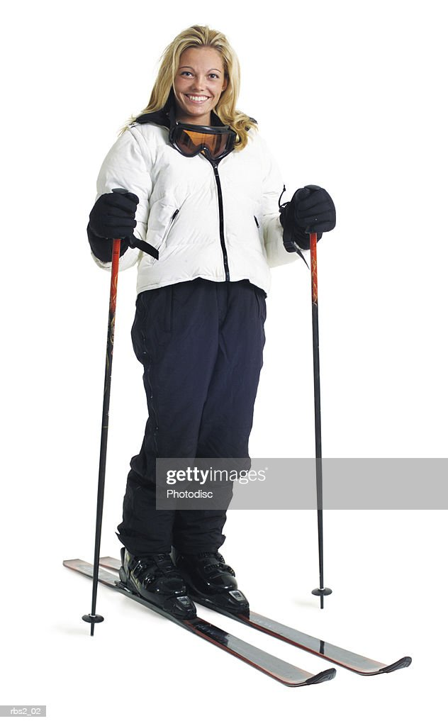 a young caucasian female skier in a white coat stands smiling with her snow skis and poles : Stock Photo
