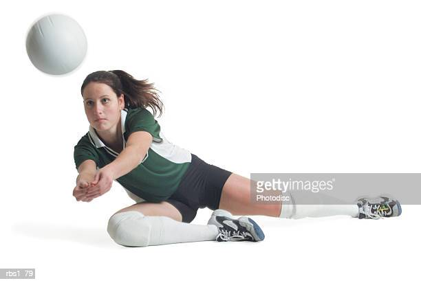 a young caucasian female volleyball player in a green and white jersey dives to the ground to hit a ball