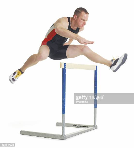 a young caucasian male athlete runs and jumps over a hurdle during a race