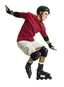 a young caucasian male in a red shirt and a black helmet rollerblades and jumps forward while balancing himself with his arms