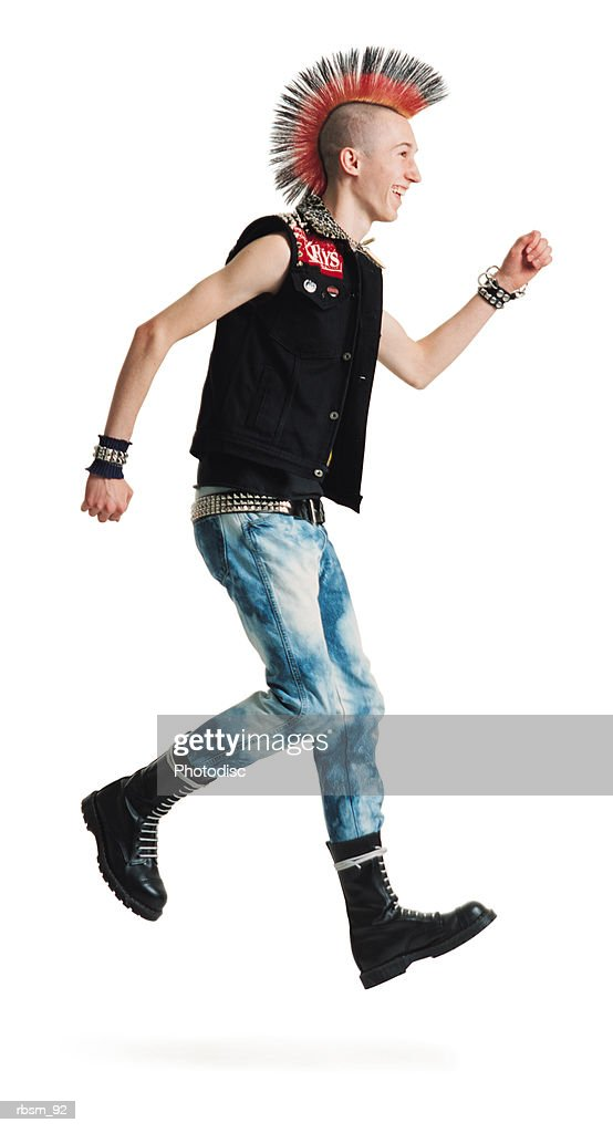 a young caucasian male punker with a colorful mohawk in jeans and black vest jumps up and smiles : Stock Photo