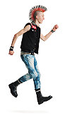 a young caucasian male punker with a colorful mohawk in jeans and black vest jumps up and smiles