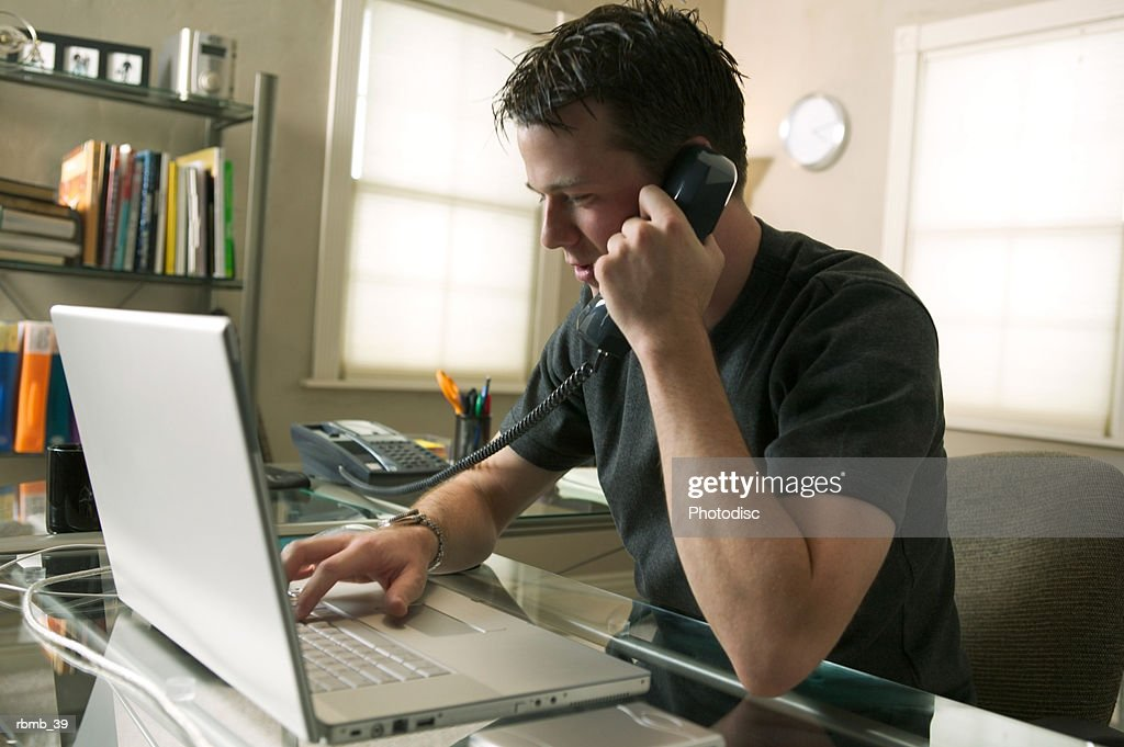a young caucasian man sits working at his computer and on the phone in his home office : Stock Photo