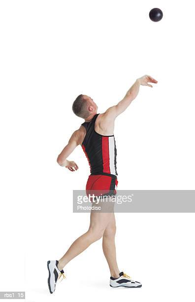 a young caucasian man wearing a red track uniform is turning around as he throws a shotput