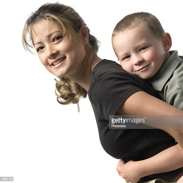 a young caucasian mother smiles as she holds her young son on her back