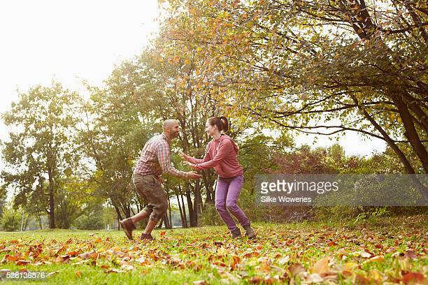 a young couple in love playing tag in a park on an autumn's day, backlit.