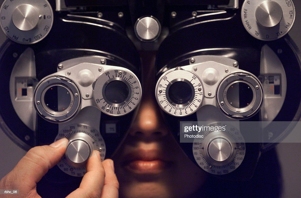 a young ethnic female sits and has her eyes checked : Stock Photo