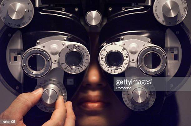 a young ethnic female sits and has her eyes checked