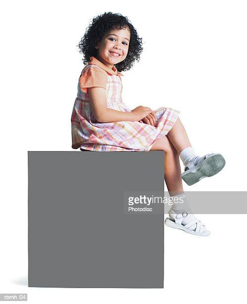 a young ethnic girl in a pastel dress sits on a blank sign and crosses her legs and smiles
