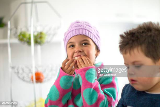 a Young girl and boy enjoying some fruit.