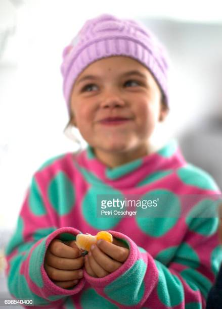 a Young girl enjoying some fruit.