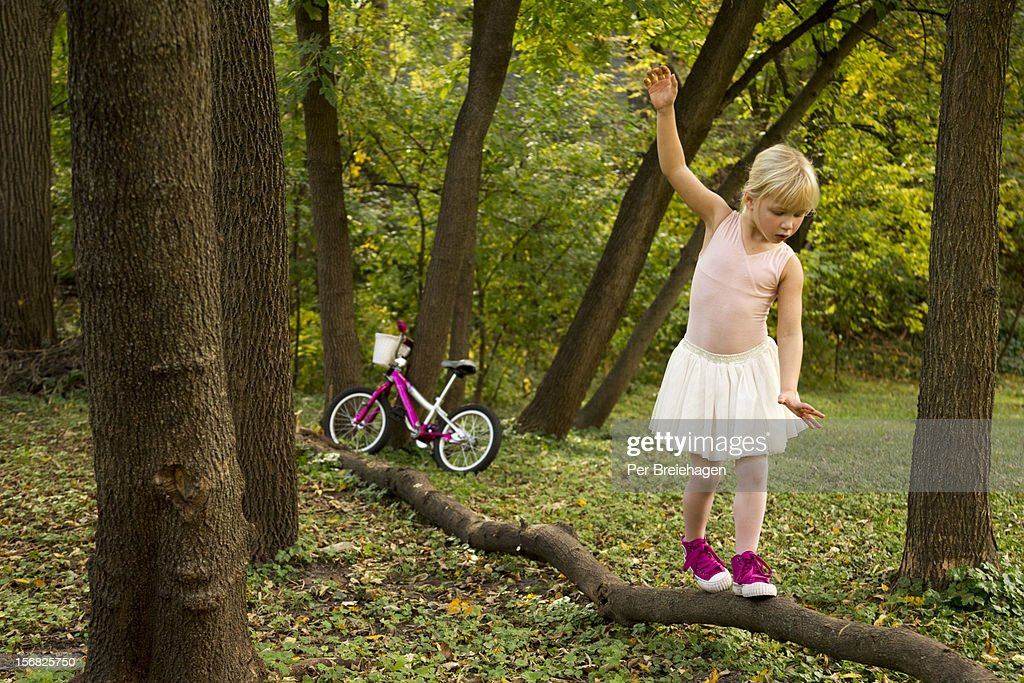 a young girl in a tutu balancing on a log : Stock Photo