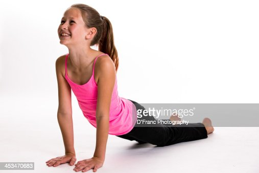 A Young Girl In Black Pants And Pink Top Does Yoga Stock