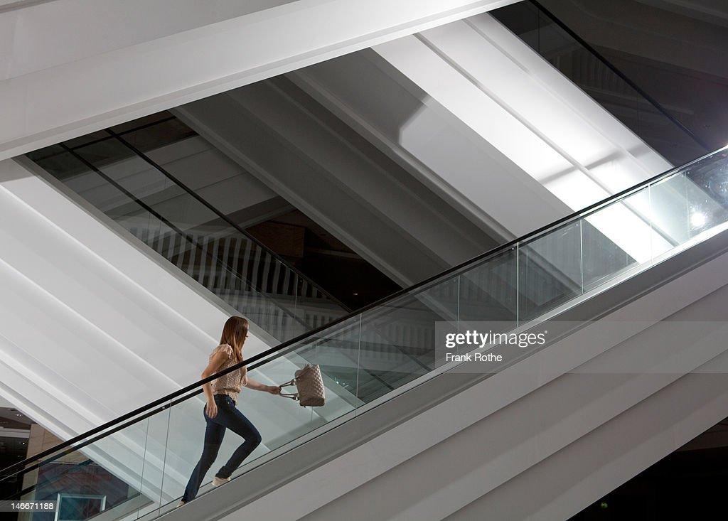 a young girl with a handbag runs up the escalator : Stock Photo