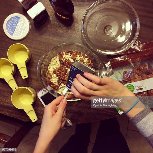 a young girl's hands preparing pecan filling for baked apples on Thanksgiving day