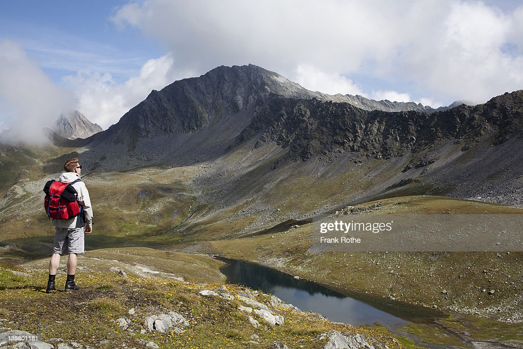 a young hiker savours the valley and mountains : Stock Photo