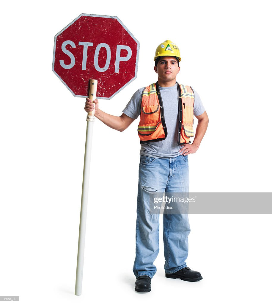 a young hispanic road construction worker stand with a stop sign : Stock Photo