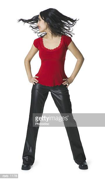 a young hispanic woman in a leather pants and a red shirt dances playfully and tosses her hair around