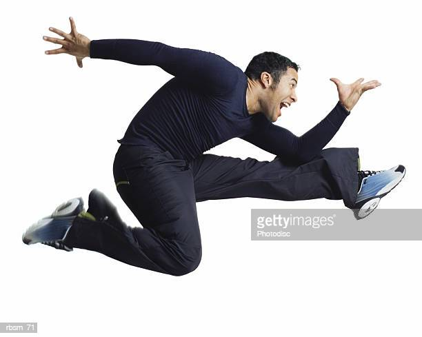 a young latin male dressed in blue jumps high and flies through the air in a running pose