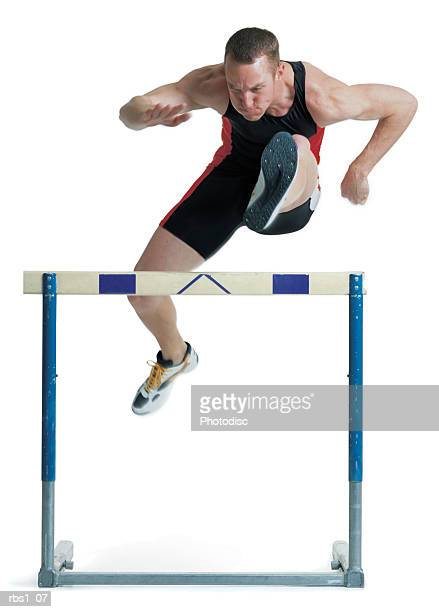 a young male caucasian runner is wearing a red and black uniform as he clears a hurdle