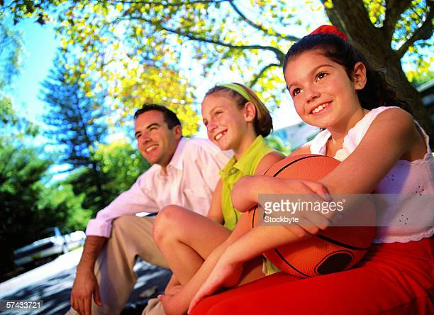 a young man and two young girls looking up smiling with a basket ball