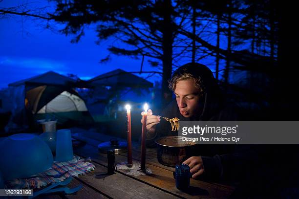 a young man eats from a pot on a picnic table at a campsite