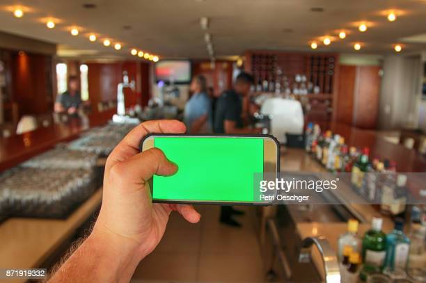 a Young man holding a green screen smartphone at a clubhouse bar.