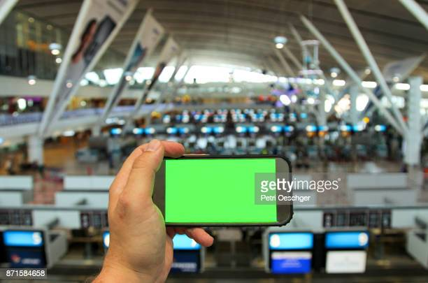 a Young man holding a green screen smartphone at Cape Town International Airport.