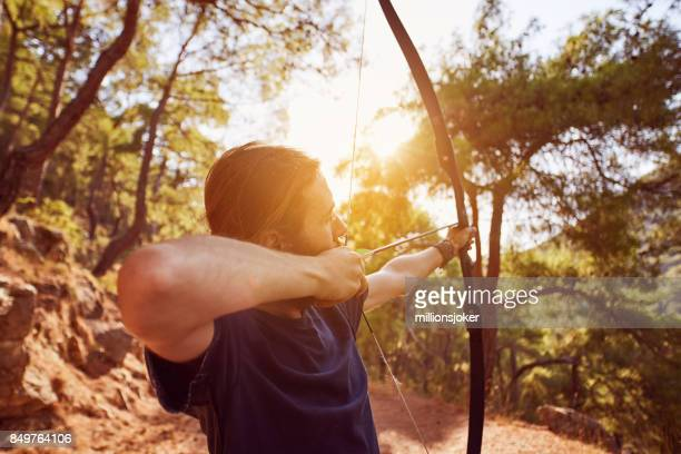 a young man is preparing to shoot with the bow in the forest
