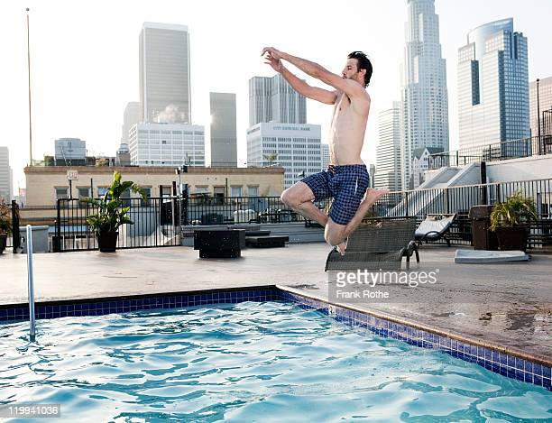 a young man jumps into his pool on a roof top