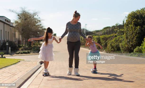 a Young pregnant woman helping two young girls skateboard.