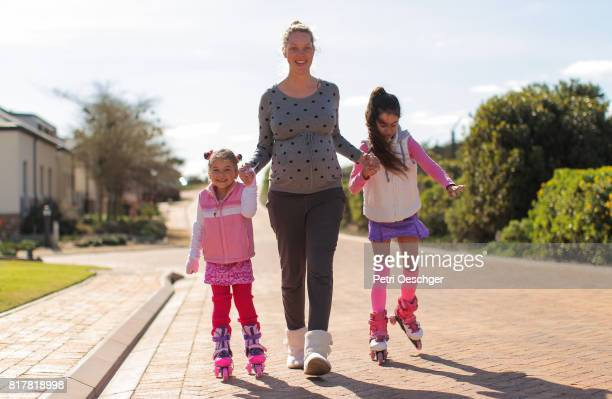 a Young pregnant woman holding hands with two young girls on rollerblades.