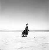 a young white female wearing a long black cloak is walking across the sand at the beach or perhaps the desert but she looks content and peaceful