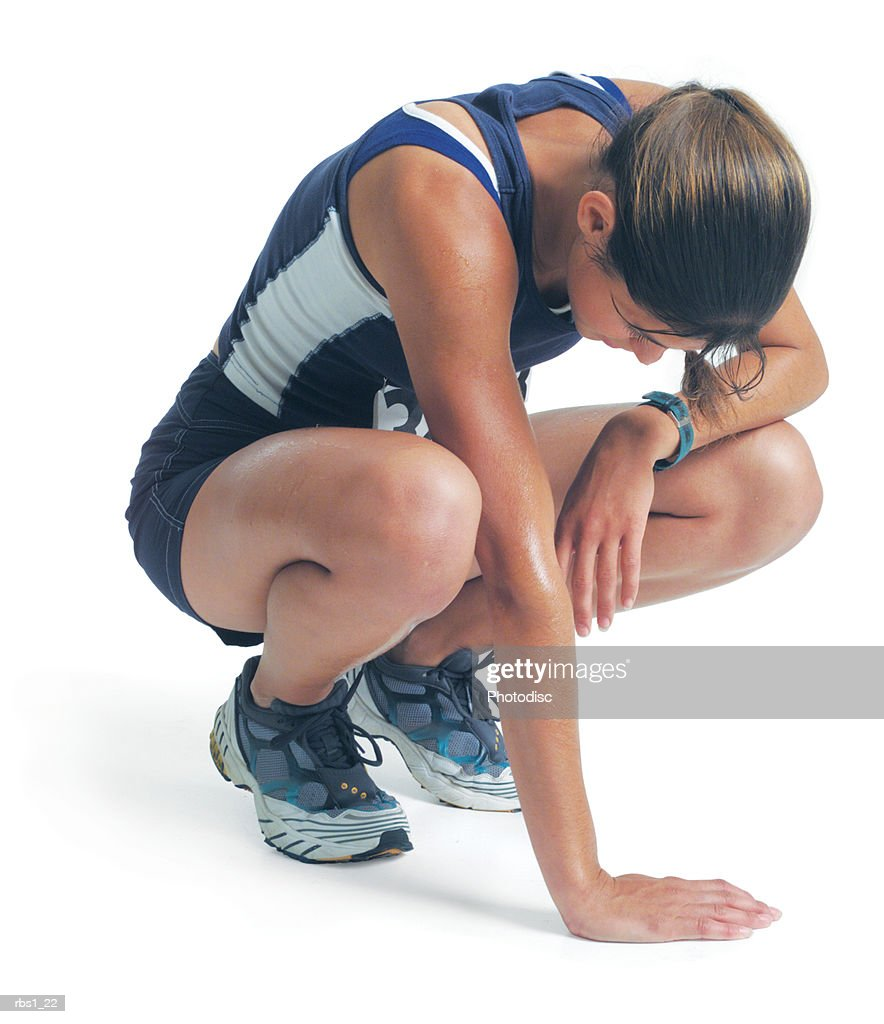 a young woman in a blue track uniform is squatting down as she leans against her knee and looks down : Stock Photo