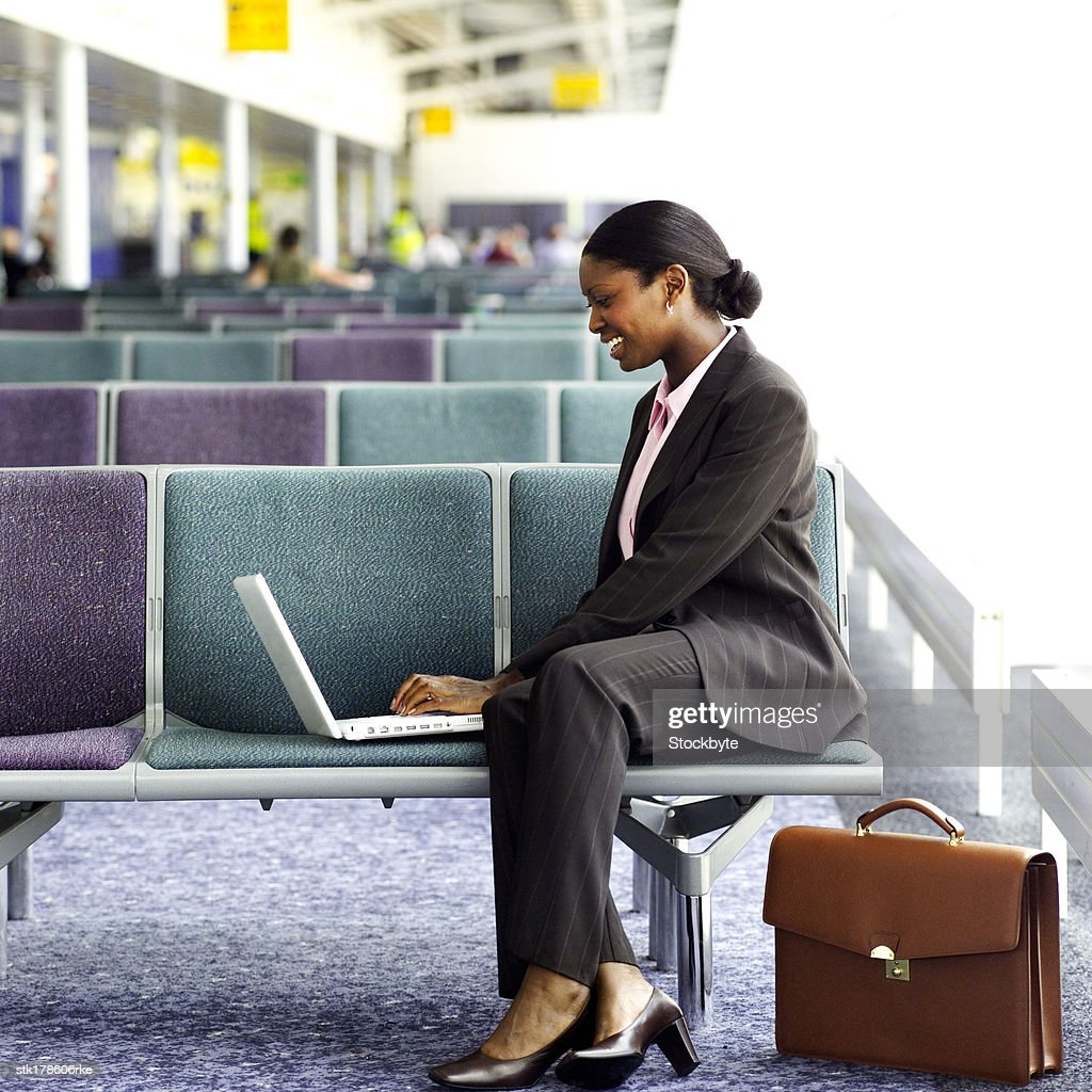a young woman sitting on waiting chairs and working on a laptop : Stock Photo