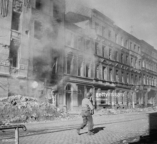 Shooting His Way Through Aachen Moving up a street in Aachen past buildings still smoking from exchanges of shots this American infantryman keeps his...
