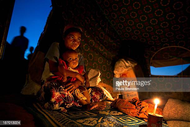 Aaisha sits in her tent with her 11 month old baby Bibi Aisha at a refugee tented camp for Rohingya IDP's November 23 2012 on the outskirts of Sittwe...