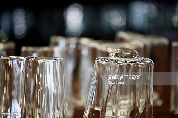 Aalto style vases created using traditional glass blowing methods sit in the workshop during manufacture at the Iittala Oyj glass factory operated by...