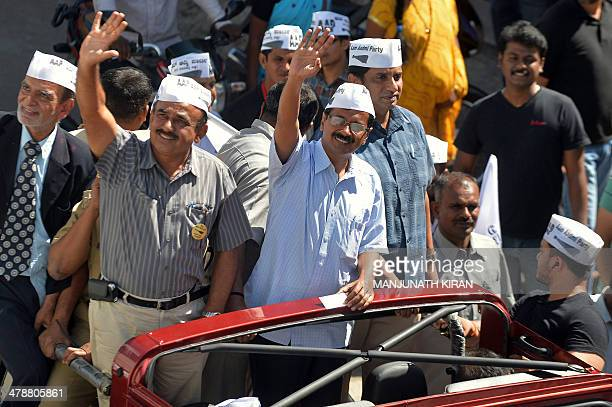 Aam Aadmi Party chief Arvind Kejriwal waves to supporters from a vehicle during a road show across Bangalore on March 15 2014 Kejriwal is on a twoday...