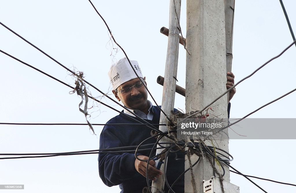 Aam Aadmi Party Convener Arvind Kejriwal restore the Electric supply from pole which was disconnected by Tata Power Delhi Distribution Ltd, due to the unpaid bill of a residence at Begam Vihar on February 8, 2013 in New Delhi, India. Arvind Kejriwal has launched 'bijli-paani satyagraha' as protest against 'inflated' power and water bills and hike in tariffs by restoring electricity connections to the households which were disconnected for non-payment of bills.