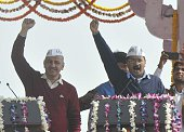 Aam Aadmi Party president Arvind Kejriwal and Manish Sisodiya wave towards crowd as after taking oath as Delhi chief minister at the Ramlila Ground...