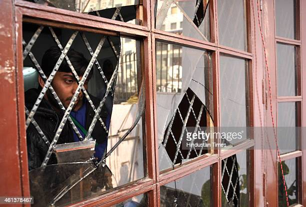 Aam Aadmi Party worker looking through the shattered window of the party office at Kaushambi after it was vandalized by the workers of Hindu Rakshak...