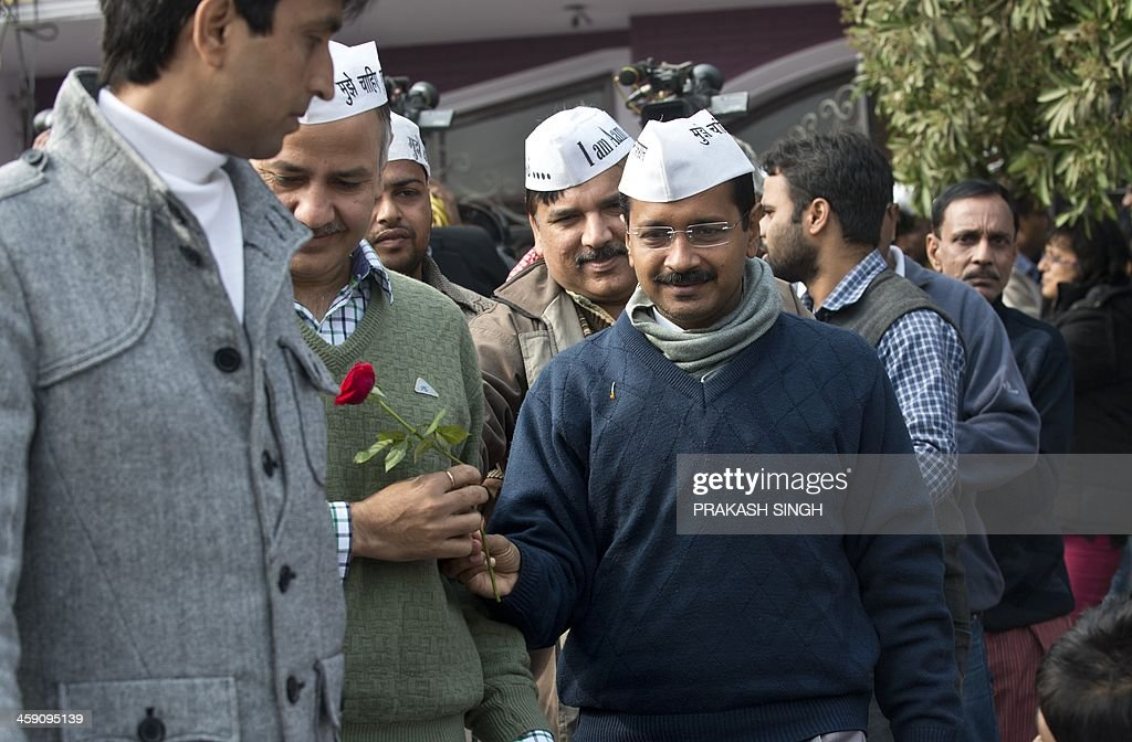 Aam Admi Party (AAP) leader Arvind Kejriwal (R) receives a rose as he arrives to address a press conference at the party headquarters in Ghaziabad, on the outskirts of New Delhi, on December 23, 2013. India's anti-corruption crusader Arvind Kejriwal announced December 23 he would head up a state government for New Delhi in a stunning breakthrough for his fledgling party just months before a general election. The former tax official is set to become chief minister in a minority administration after his Aam Aadmi party won the second highest number of seats in the state assembly earlier this month. AFP PHOTO/Prakash SINGH
